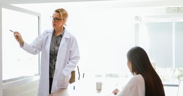 Artsen of wetenschappers onderwijzen en verklaren studenten en patiënten die aan boord schrijven