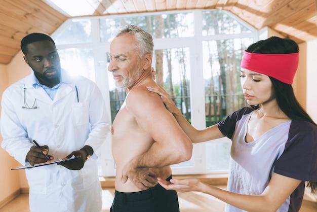 Artsen onderzoeken een oudere man met rugpijn in zijn rug.