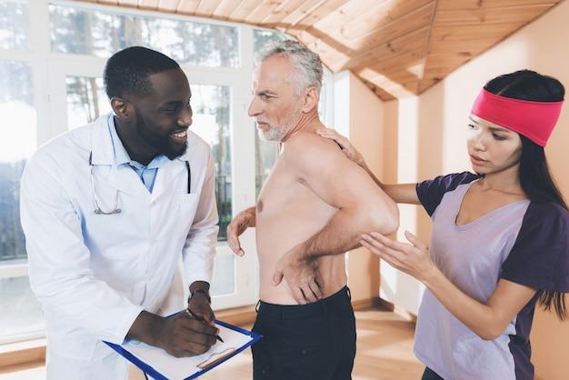 Artsen onderzoeken een oudere man met rugpijn in zijn rug