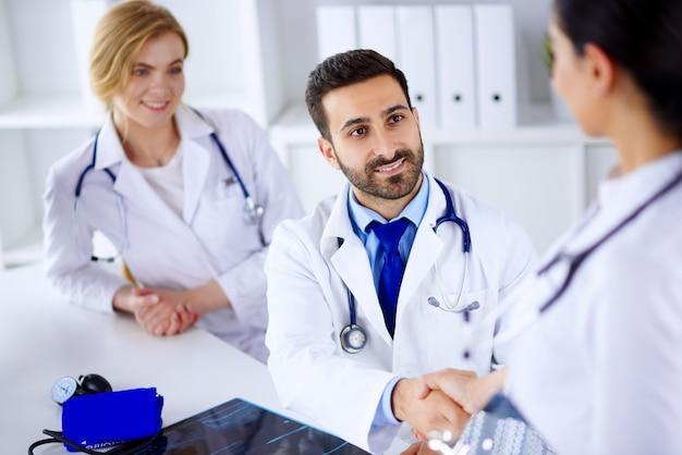 Artsen op kantoor bespreken de diagnose van een patiënt. bijeenkomst van artsen op kantoor. artsen schudden elkaar de hand