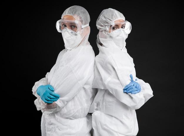 Artsen poseren terwijl ze beschermende kleding dragen