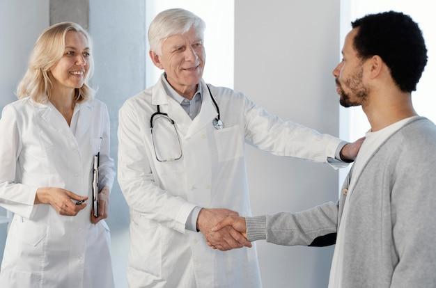 Artsen praten met een jonge patiënt
