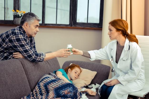 Artsen recept. aardige knappe man die naar de dokter kijkt terwijl hij een fles met pillen neemt