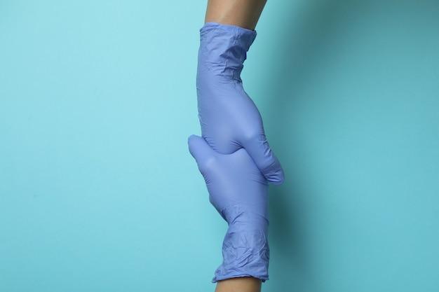 Artsen schudden handen in medische handschoenen op blauwe geïsoleerde achtergrond