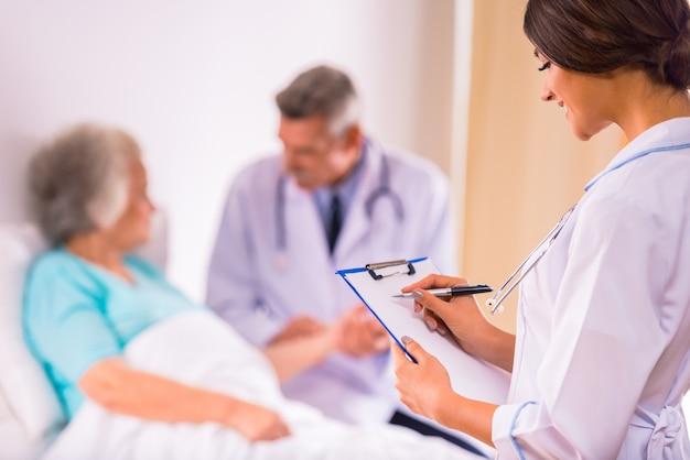 Artsen staan voor een bejaarde grootmoeder.