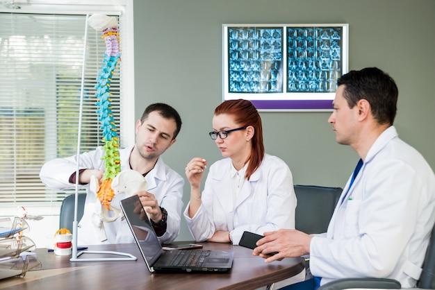 Artsen team met medische raad in het ziekenhuis. medische problemen bespreken. spine fixatiesystemen