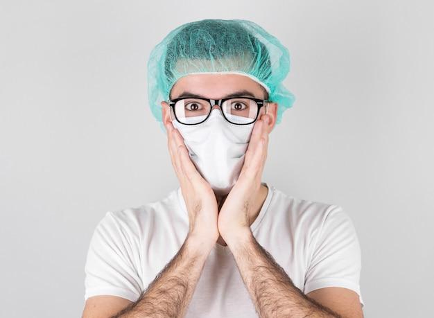 Artsenchirurg in wit medisch masker en een medisch glb bevindt zich op witte achtergrond