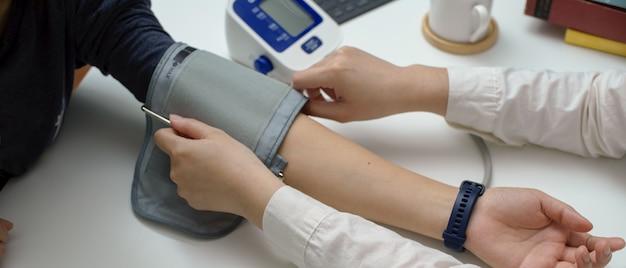 Artsendruk die haar patiënt met bloeddrukmonitor meten in onderzoeksruimte