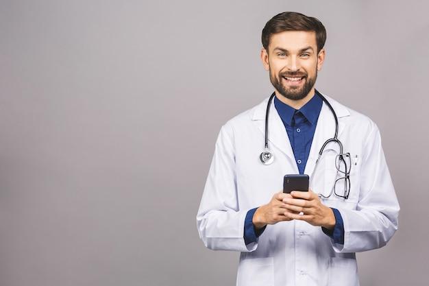 Artsenhanden die op een slimme telefoon texting die op een grijze achtergrond wordt geïsoleerd.