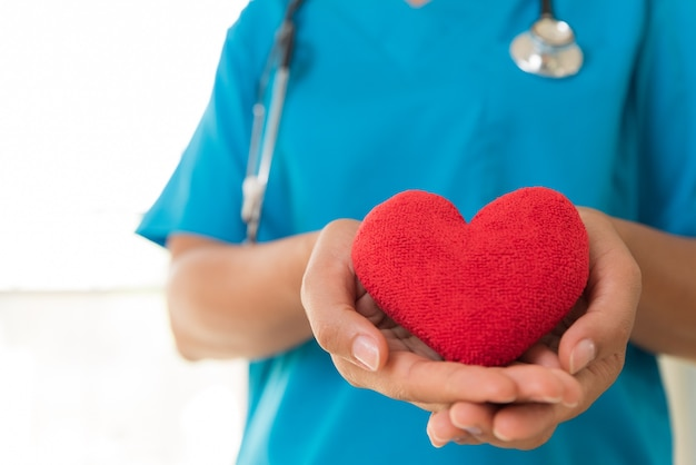 Artsenhanden die rood hart houden. gezondheidszorg concept.