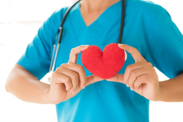 Artsenhanden die rood hart houden. gezondheidszorg en medische concept.