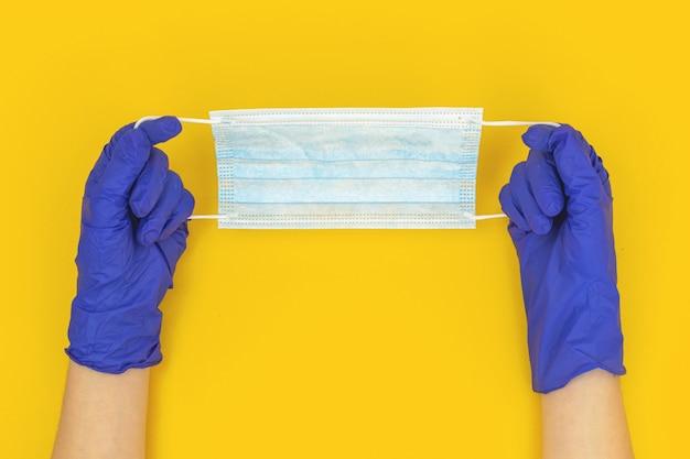 Artsenhanden met medisch masker op een gele achtergrond, concept de covid-19-preventie