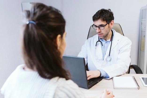 Artsenmannetje die aan geduldig wijfje spreken bij de artsen raadplegen. medisch concept
