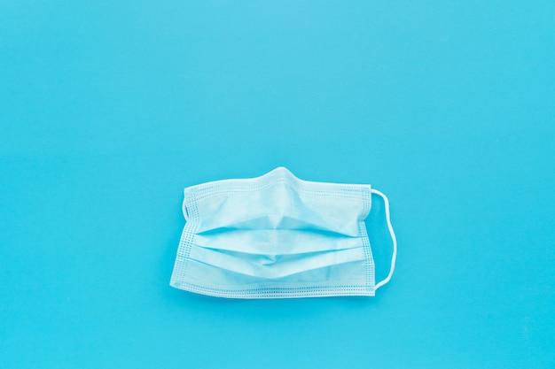 Artsenmasker op blauwe achtergrond, sociale afstand om covid-19 verspreide campagne te verhinderen