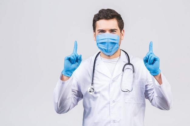 Artsenmens in medische het maskerhandschoenen van het toga steriele die gezicht op witte muur wordt geïsoleerd. epidemie pandemisch coronavirus 2019-ncov sars covid-19 griepvirus. wijsvinger opzij.
