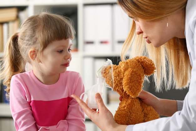 Artsenspel met weinig patiënt die inhalator geeft aan speelgoed