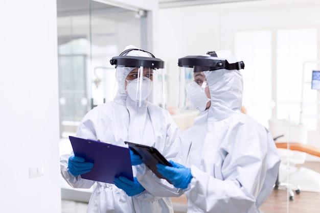 Artsenteam dat een beschermend pak draagt om covid-19 te bestrijden terwijl ze naar elkaar kijken. medische collega's die professionele uitrusting dragen tegen infectie met coronavirus als veiligheidsmaatregel.