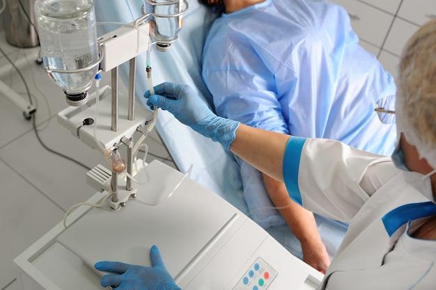 Artsenvrouw die in medisch masker en steriele handschoenen een patiënt voorbereiden op chirurgie