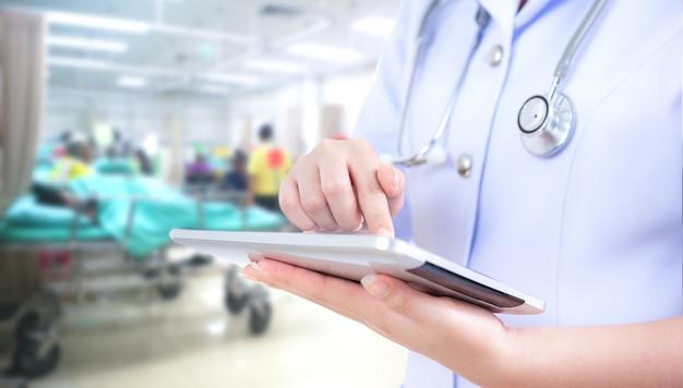 Artsenvrouw die tabletcomputer met behulp van
