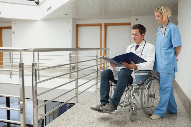 Artsenzitting in rolstoel die nota's met verpleegster onderzoeken