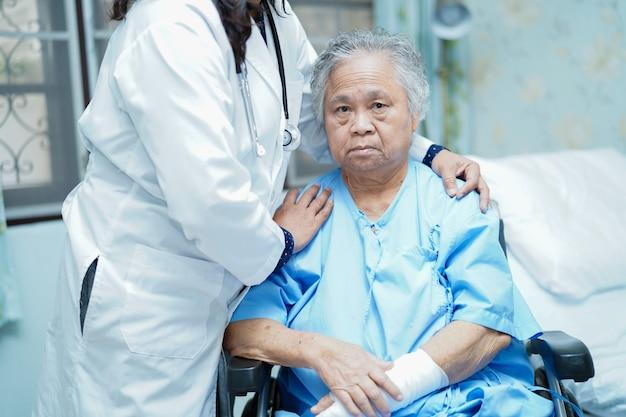Artsenzorg, hulp en steun hogere vrouwenpatiënt in rolstoel bij het ziekenhuis.