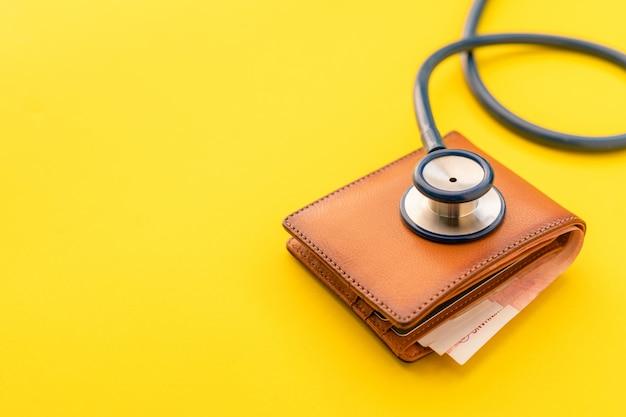 Artsstethoscoop en de nieuwe portefeuille van leer bruine mannen op geel. begroting voor gezondheidscontrole of geld en financieel concept
