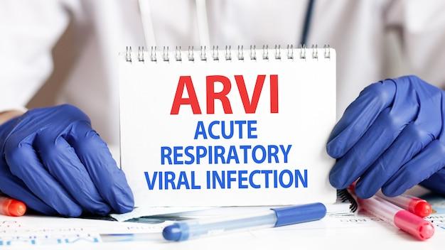 Arvi-kaart in handen van arts. de arts dient blauwe handschoenen in met een vel papier met de tekst arvi - afkorting voor acute respiratory viral infection, medisch concept.