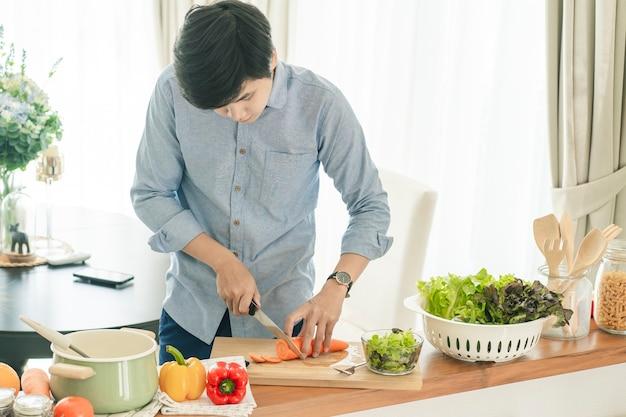 Asain man koken in de huiskeuken.