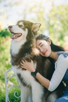Asain vrij jonge vrouw die haar hond koestert