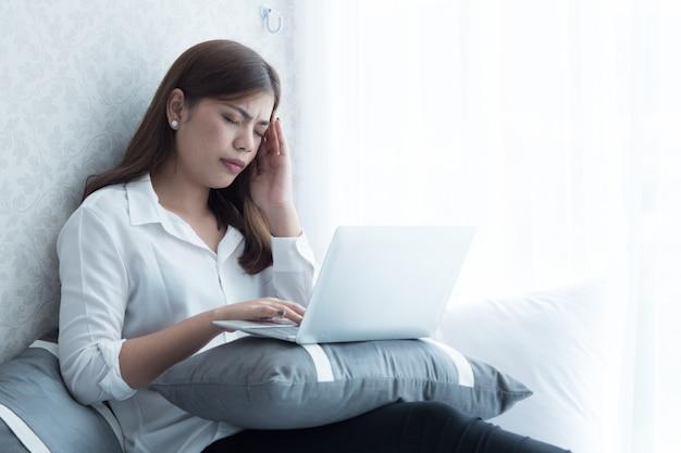 Asain vrouw heeft koorts. ze heeft hoofdpijn tijdens het gebruik van de laptop in de slaapkamer.