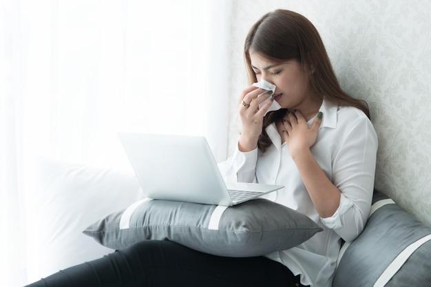 Asain vrouw heeft koorts. ze niest tijdens het gebruik van de laptop in de slaapkamer.