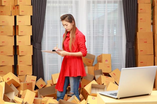Asain vrouw in rode jurk werkt thuis, online winkelbedrijf