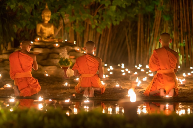 Asalha puja day, monniken steken kaarsen aan en bidden tot boeddhabeeld in phan tao tempel, chiang mai, thailand