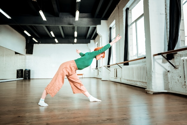 Asana uitrekken. aangenaam uitziende, fitte yoga-instructeur die een groene coltrui draagt en asana doet om uit te rekken