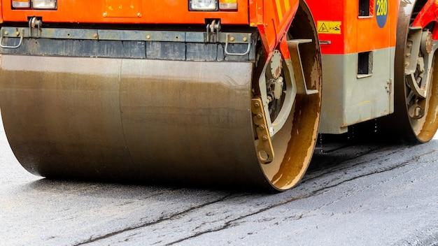 Asfaltafwerkmachine op de weg tijdens asfaltverdichting close-up. weg reparatie. een nieuwe weg aanleggen