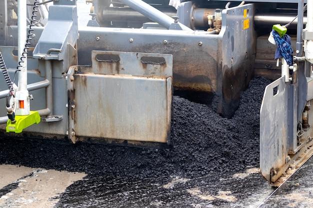 Asfaltafwerkmachine op de weg tijdens het leggen van asfalt, een deel van de auto close-up. weg reparatie. een nieuwe weg aanleggen