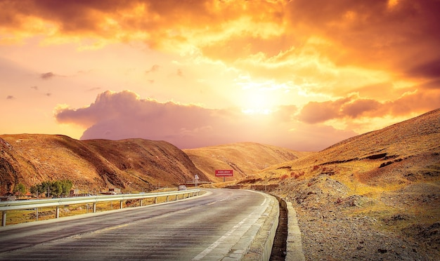 Asfaltweg en bergen bij prachtige zonsondergang