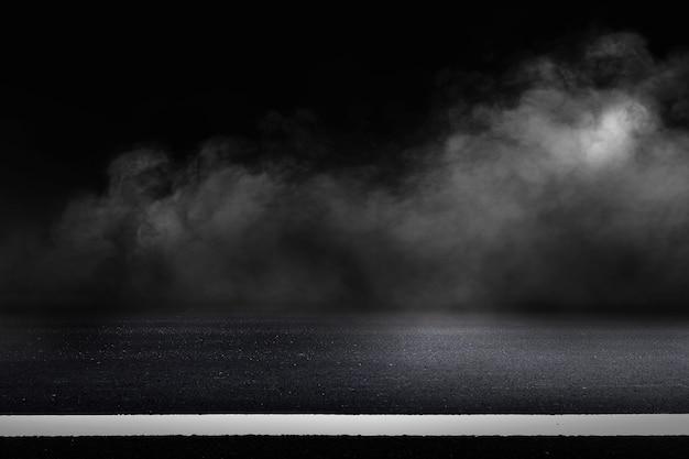 Asfaltweg en donkere hemelachtergrond