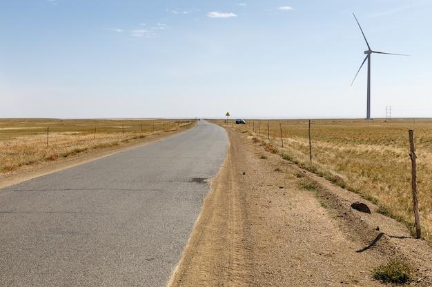Asfaltweg in de steppe met windgenerator op de horizon, binnenmongolië