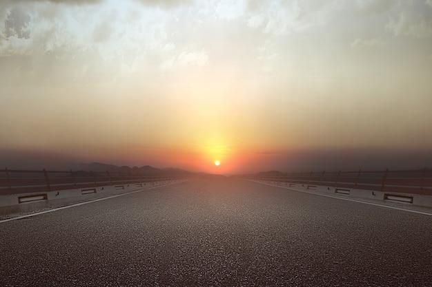 Asfaltweg met een zonsopganghemel achtergrond