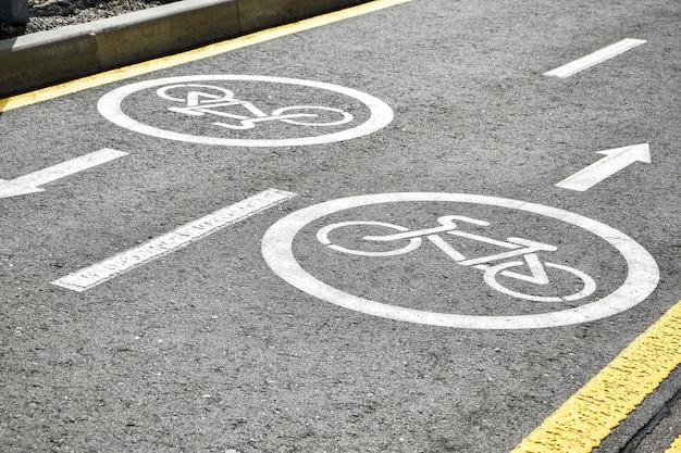 Asfaltweg met fiets en elektrische transportbaan. cyclus en emissievrije voertuigen wit bord op de vloer. recreatiegebied voor vervoer van groene energie in stadspark