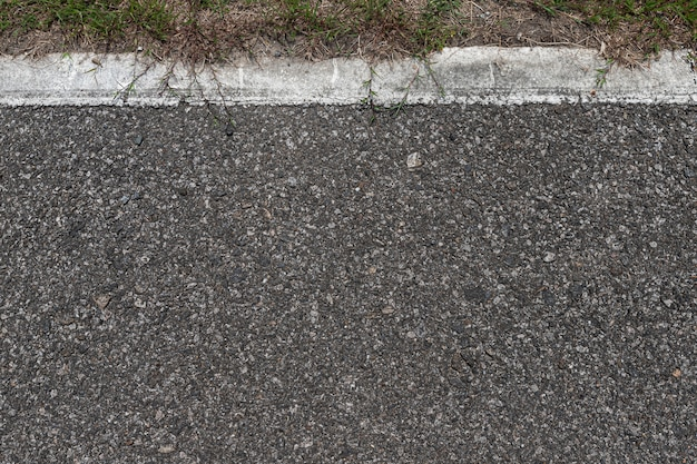 Asfaltweg met strepen en groen gras textuur achtergrond, lege kopie ruimte.