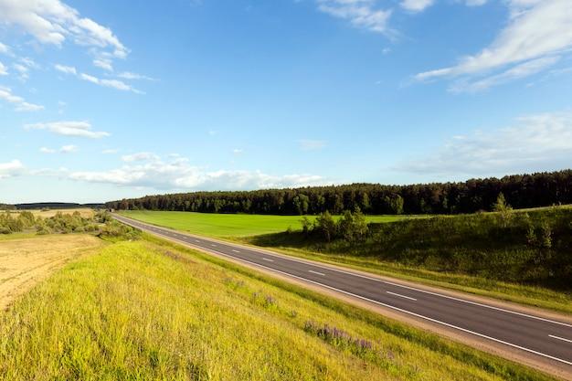 Asfaltweg waarlangs groen gras en bomen groeit. landschap met blauwe lucht in de zomer. foto vanaf een heuvel