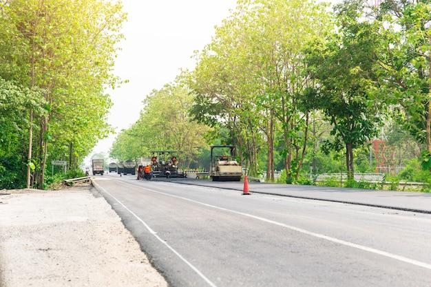 Asfaltwegconstructie met machine en stoomwalsvrachtwagen bij snelweg in thailand.