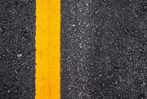 Asfaltwegdek met gele lijn