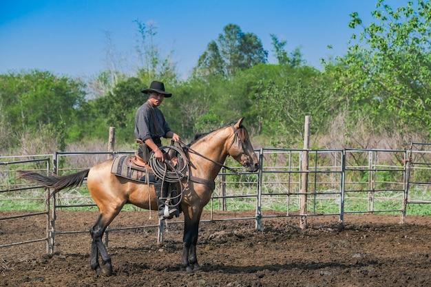 Asian man cowboy is een kalf aan het vangen om in een ranch te worden gebrandmerkt