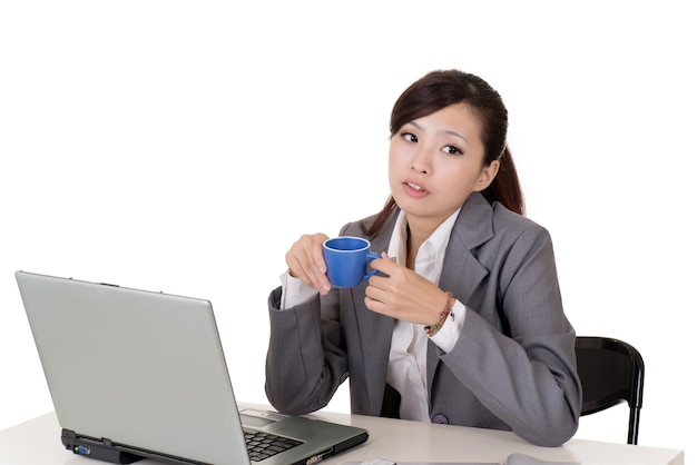 Asianbusiness vrouw werken en denken met laptop op bureau tegen witte achtergrond.