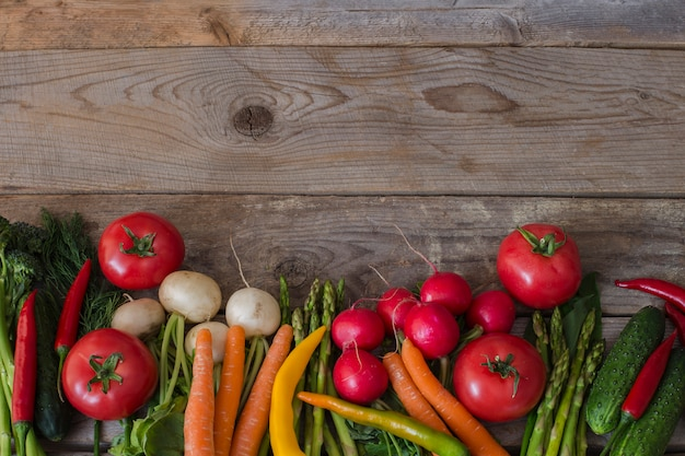 Asperges, broccoli, chili, tomaat, radijs, wortelen en dille - achtergrond van groenten