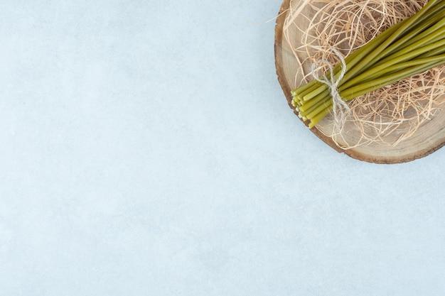 Asperges en stro op een bord, op de marmeren tafel.
