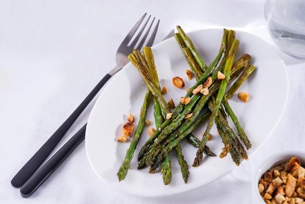 Asperges geroosterd in olijfolie met gemalen walnoten en saus op een witte plaat. vegetarisch eten.